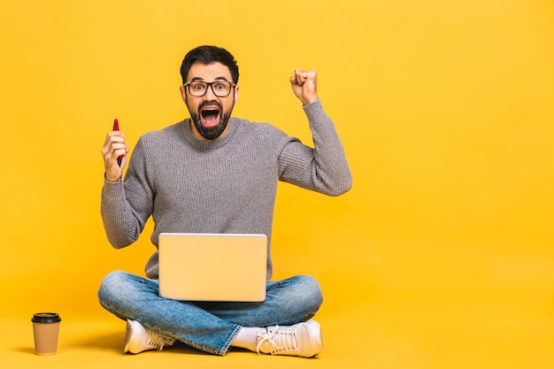 Happy winner! man sitting on the floor with laptop and talking at phone. isolated over yellow background.