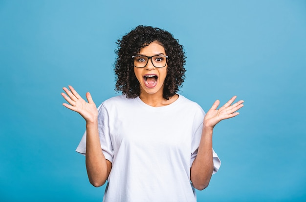 Happy winner! photo of cheerful beautiful young african american woman standing isolated over blue wall background. looking camera showing winner gesture.