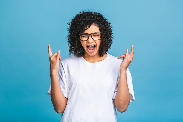 행복한 우승자! 파란색 벽 배경 위에 고립 된 서 쾌활 한 아름 다운 젊은 아프리카 계 미국인 여자의 사진. 승자 제스처를 보여주는 카메라를 찾고 있습니다.