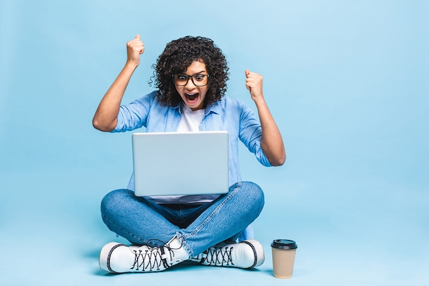 Happy winner. portrait of african american black woman in casual sitting on floor in lotus pose and holding laptop isolated over blue background
