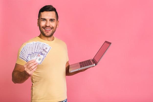 ラップトップとお金を保持している興奮した若いカジュアルな男の幸せな勝者の肖像画