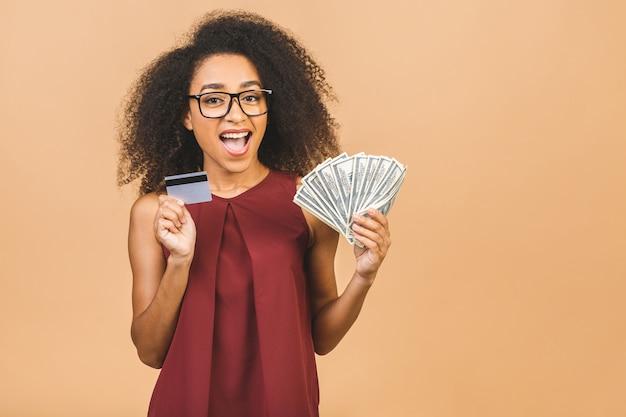 Счастливый победитель. портрет успешной женщины 20 лет с афро-прической, держащей много денег