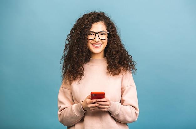 Счастливый победитель! портрет удивленной изумленной улыбающейся случайной курчавой студентки, держащей смартфон, изолированную на синем фоне.
