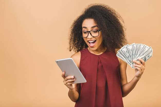 Happy winner. portrait of successful business woman with afro hairstyle holding lots of money