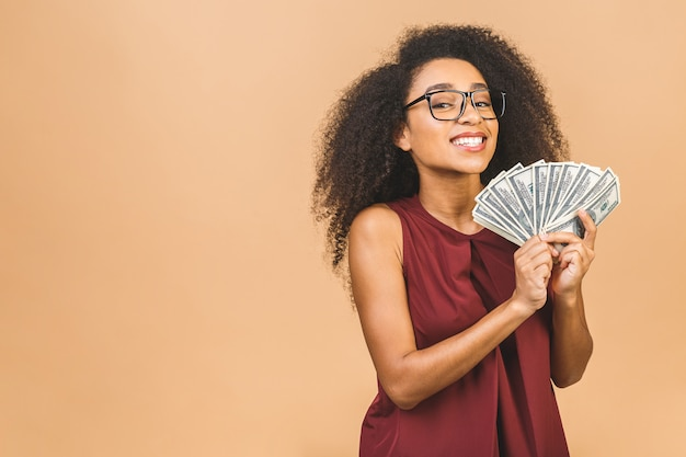 Happy winner. portrait of successful woman 20s with afro hairstyle holding lots of money