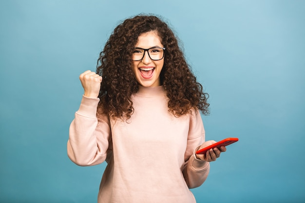Happy winner! portrait of surprised amazed smiling casual curly student woman holding smartphone isolated over blue background.