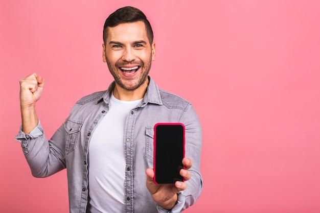 Счастливый победитель молодой красавец показывает экран смартфона с неожиданным лицом