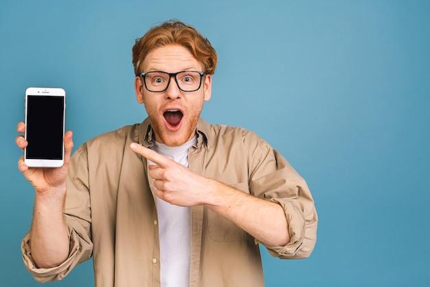 Счастливый победитель! молодой красивый потрясен изумленный мужчина показывает экран смартфона с неожиданным лицом