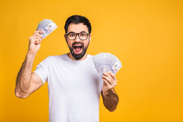 Happy winner! young rich man in casual holding money dollar bills with surprise isolated over yellow background.