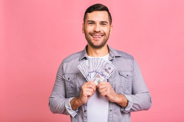 Счастливый победитель молодой богатый человек в непринужденной обстановке держит долларовые банкноты с сюрпризом