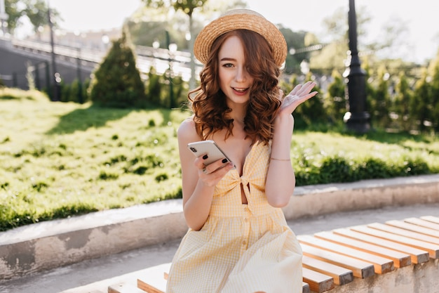 電話でベンチに座っている波状の赤い髪の幸せなwinsome女の子。公園で朝を過ごす熱狂的な生姜の女性の屋外の肖像画。