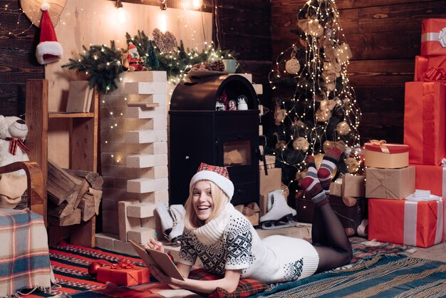 Happy winter holidays at cozy decorated home with family teenage blonde girl in knitted sweater dres...