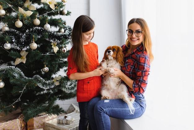 幸せな冬の休日!ポジティブなブルネットの女性は、部屋の床、近くの犬、クリスマスツリーの近くで楽しい贈り物で小さな女の子のポーズを受け入れます。