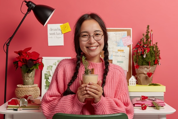 Happy winter holidays, rest, home, drinks concept. cute tender woman in big transparent glasses drinks delicious christmas cocktail, enjoys cozy atmosphere, desktop with notes, firtree in bakground