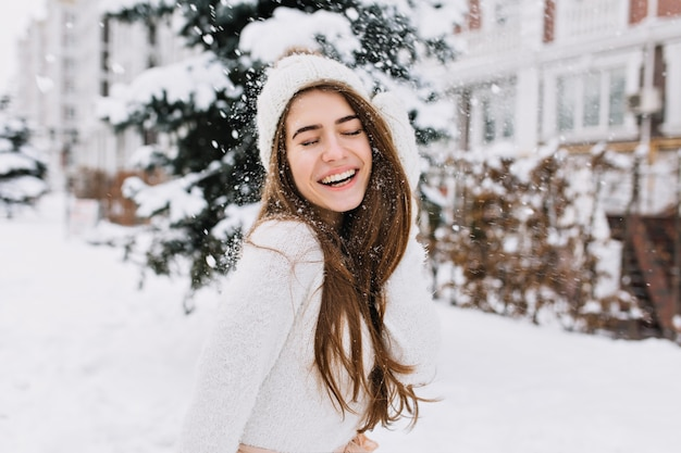 Happy winter moments of joyful young woman with long brunette hair, white winter clothes having fun on street in snowing time. expressing positivity, true brightful emotions, smiling with closed eyes.