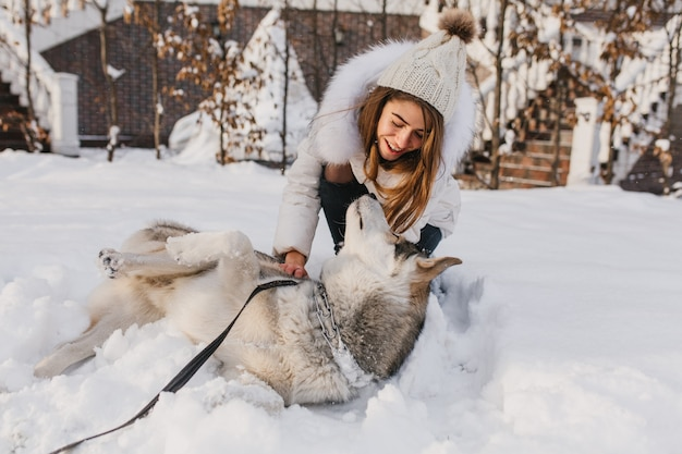 Happy winter time of joyful young woman playing with cute husky dog in snow on street. cheerful mood, positive emotions, real friendship with pets, love animals