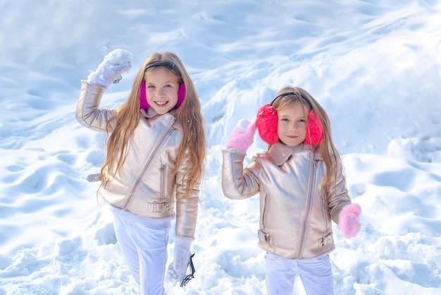 행복한 겨울 시간 공원에서 눈을가지고 노는 두 어린 소녀 두 어린 소녀의 초상화와 함께 재생...