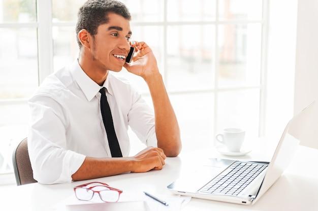 Доволен бизнесом. счастливый молодой афро-американский мужчина в строгой одежде, глядя на монитор компьютера
