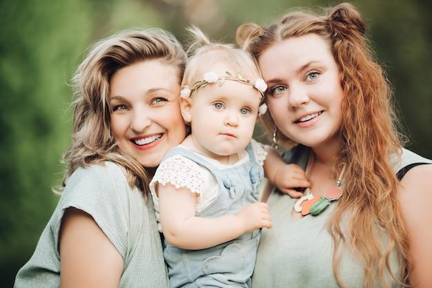 그린 트리 배경에서 야외에서 함께 포즈 웃 고 여자와 행복. 웃는 어머니와 아버지가 부모가 즐기는 어린이를 들고