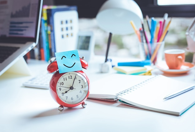 Happy with job or monday morning concepts smile face with note on clockno people
