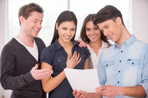 Результатом доволен. группа веселых молодых людей, стоящих рядом и улыбающихся, пока мужчина держит в руках бумагу