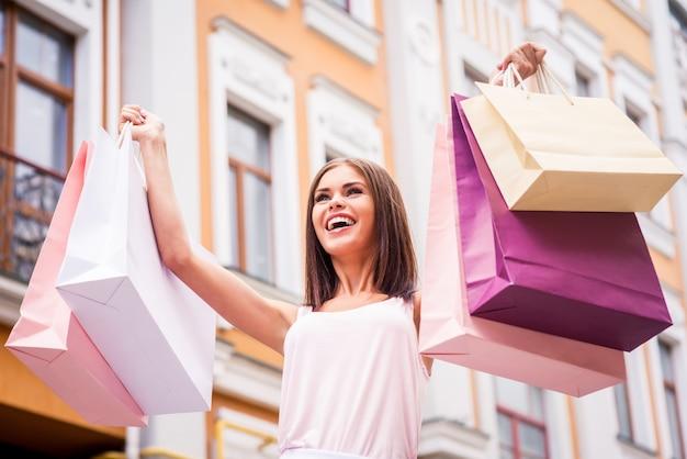 하루 쇼핑 후 행복 한 여자입니다. 야외에 서서 쇼핑백을 들고 웃고 있는 아름다운 젊은 여성의 낮은 각도