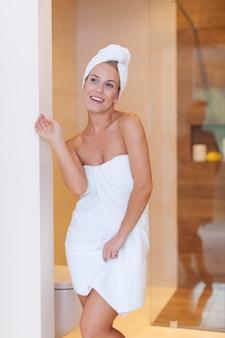 朝のシャワーの後の幸せな女性