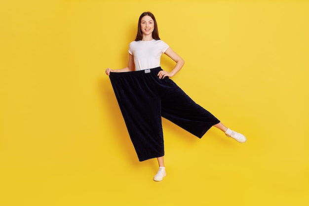 Happy woman after weight loss posing on one hand isolated over yellow wall, wearing white casual t shirt and too big black pants, keeps one hand on hip, rejoices at achieved result.
