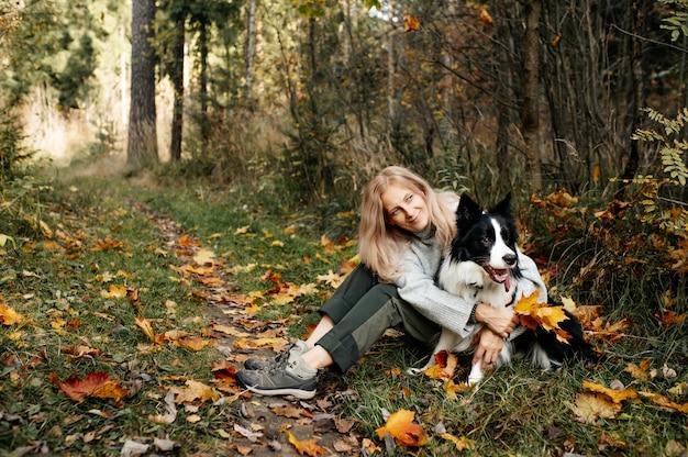 幸せな女性と秋の森の黒と白のボーダーコリー犬