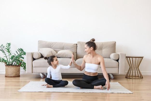 Счастливая женщина и ребенок вместе делают упражнения йоги дома на полу гостиной, растягивая диван, давая друг другу пять рук