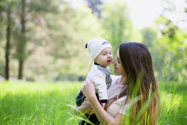 행복 한 여자와 피 봄 정원에서 아이. 아이 키스 여자. 어머니의 날 휴가 개념