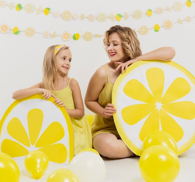 Счастливая женщина и девушка позирует с лимонными украшениями