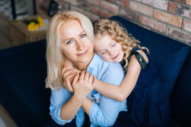 Счастливая женщина и ее кудрявая маленькая дочь обнимаются дома в уютной гостиной