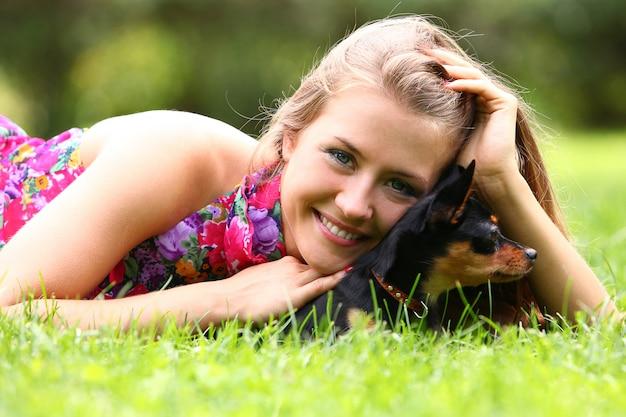 Счастливая женщина и ее милая собака на траве