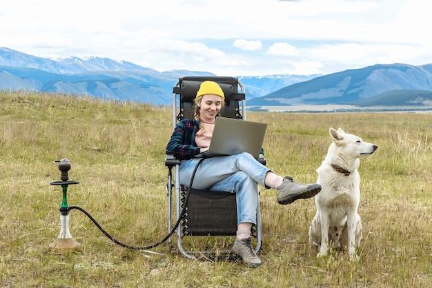 행복한 여성과 그녀의 개가 앉아서 노트북으로 온라인 작업을 하고 휴가 중에 산에서 인터넷을 사용하고 있습니다. 프리미엄 사진
