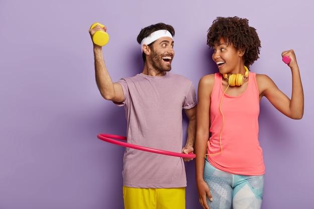 Счастливая женщина и мужчина делают упражнения в помещении, тренируют бицепсы, одеты в активную одежду