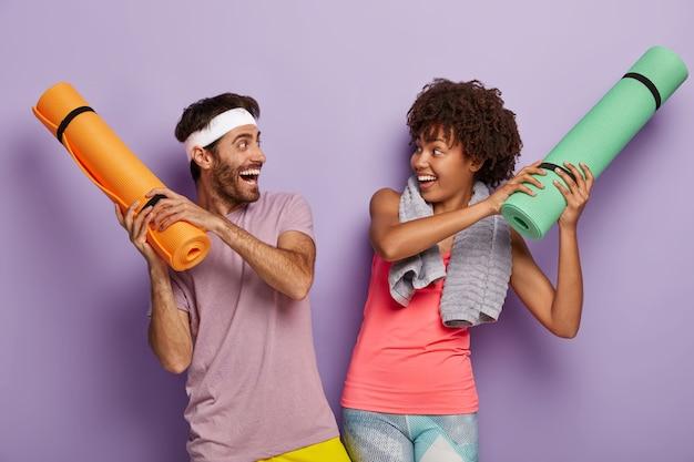 幸せな女性と男性は遊び心のある気分を持ち、表情を喜ばせ、カレマットを巻き上げ、カジュアルな服装をしています