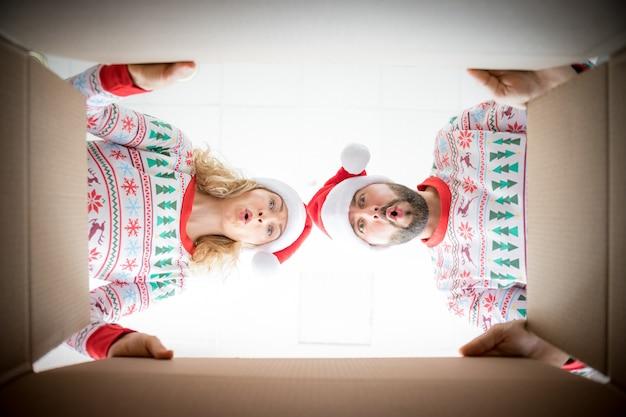 幸せな女と男が箱を覗き込んでいます。面白い驚きのカップルがクリスマスプレゼントボックスを開梱します。クリスマスの休日の概念。ローアングルビュー。