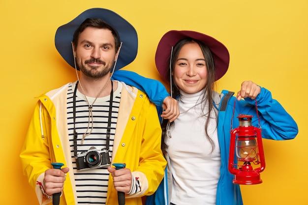 행복한 여자와 남자 관광객은 여름 휴가를 적극적으로 보내고, 도보로 걷고, 긴 목적지를 커버합니다.