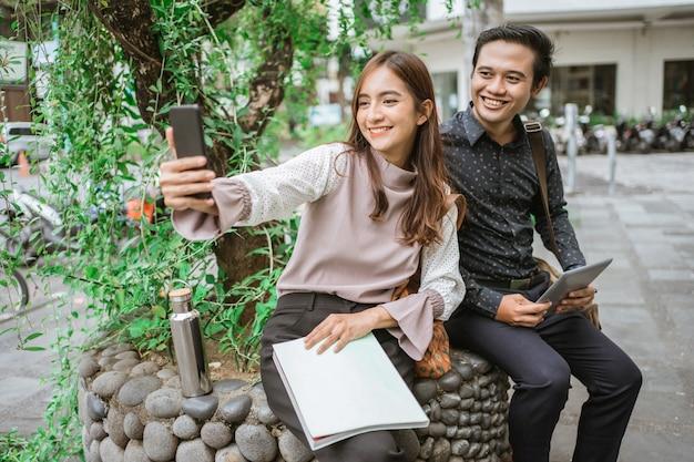自撮り写真を撮るスマートフォンを使用して幸せな女性と男性