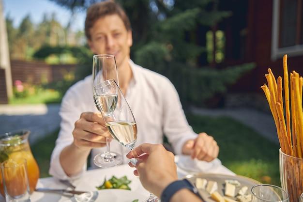 彼らの会議を楽しみながら屋外に座ってワインのグラスを持つ幸せな女性と男性