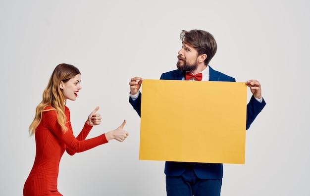 明るい背景のポスターのモックアップに黄色の紙の幸せな女と男