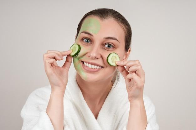 幸せな女性は彼女の頬にキュウリのスライスでフェイスマスクを適用しました