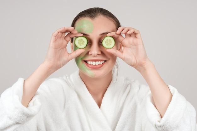 幸せな女性は彼女の目にキュウリのスライスで、彼女の顔にマスクを適用しました