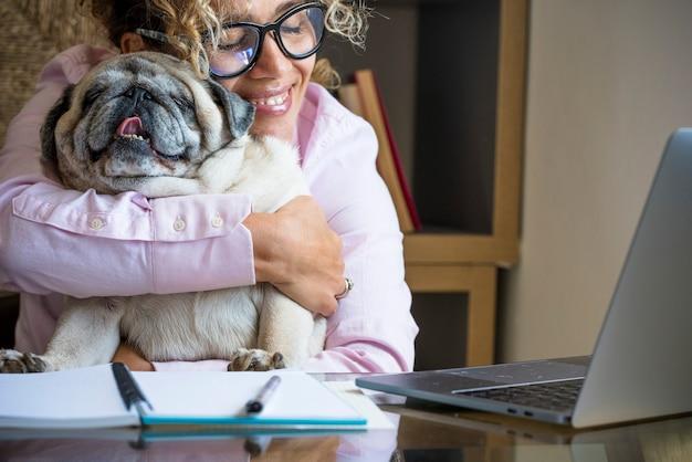 デスクトップ上のコンピューターのラップトップで仕事をしている間、彼女の親友のパグ犬を愛している自宅で幸せな女性-愛のライフスタイルの動物を持つスマートな作業とオンラインの仕事の女性