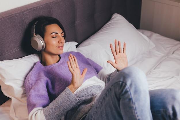 따뜻한 옷 풀오버를 입고 편안한 침대에 집에서 행복한 여자, 음악 듣기