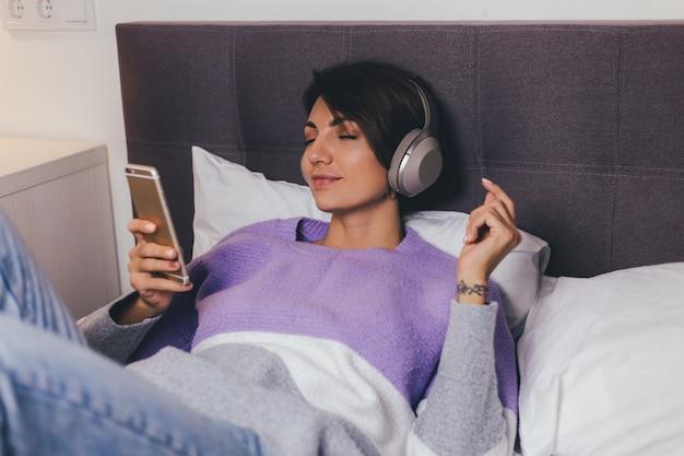 暖かい服のプルオーバーを着て快適なベッドで自宅で幸せな女性、音楽を聴く