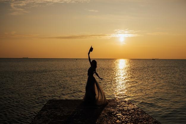 Счастливая женщина на летнем закате на море поднимает руки к оранжевому небу.