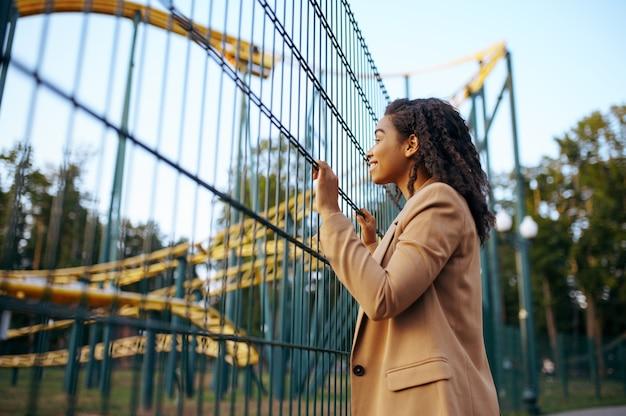 Счастливая женщина на аттракционе американских горок в парке развлечений. влюбленная пара расслабиться на открытом воздухе. семейный отдых летом, развлекательная тематика