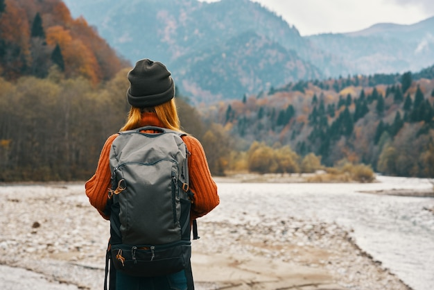 Happy woman in autumn forest in the mountains outdoors with a backpack on her back travel tourism. high quality photo